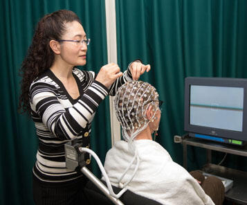 Chuan Hou setting up EEG work in the lab.